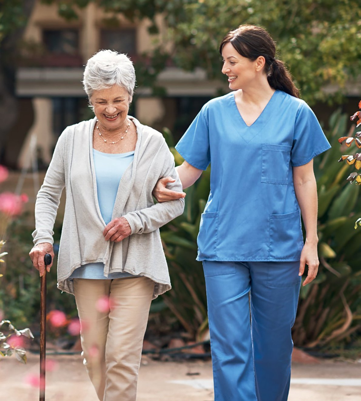 assisted living facility worker taking elder resident on a stroll