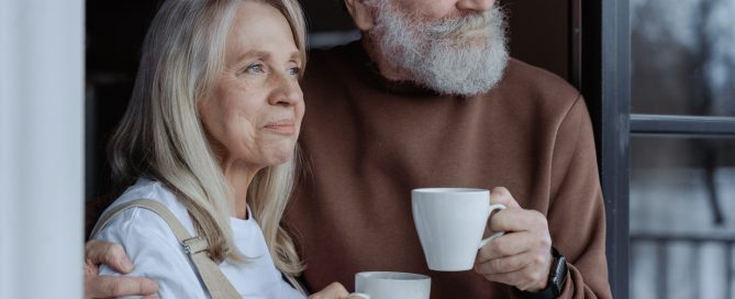 old couple holding cups of coffee